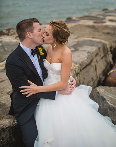 Newlywed couple kissing on the shoreline by Jersey Shore Photographer Meghan Burke